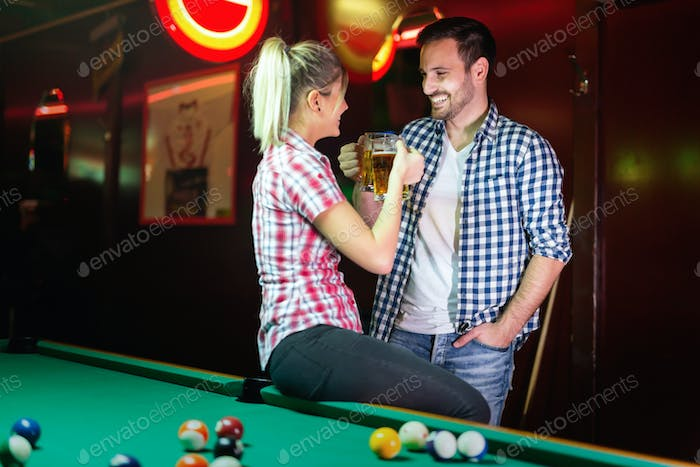 Happy couple drinking beer and playing snooker