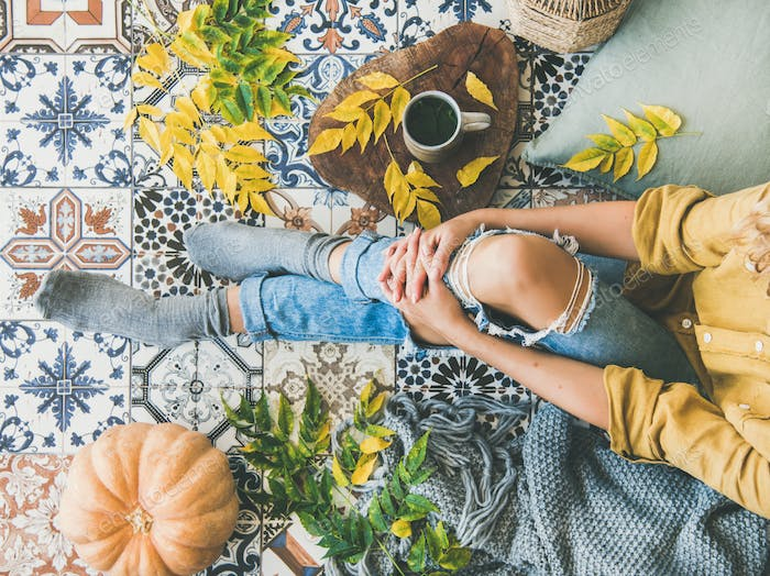 Female sitting on balcony with Autumn leaves, food, herbal tea