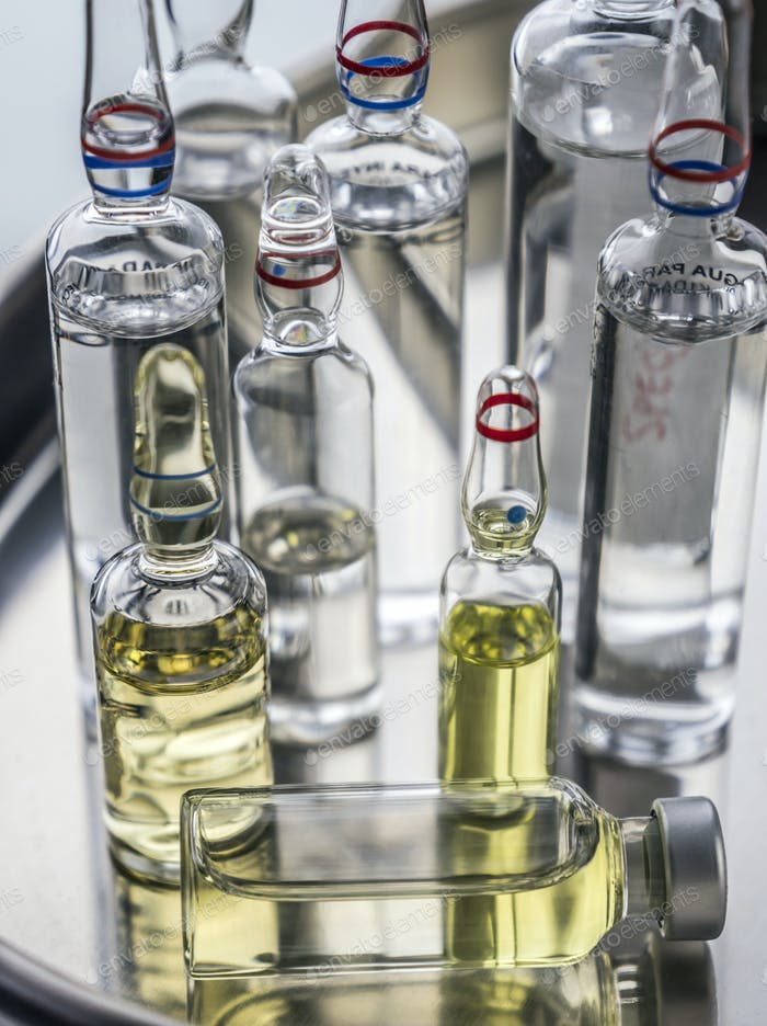 Different types of medical vials on a tray in a laboratory, conceptual image