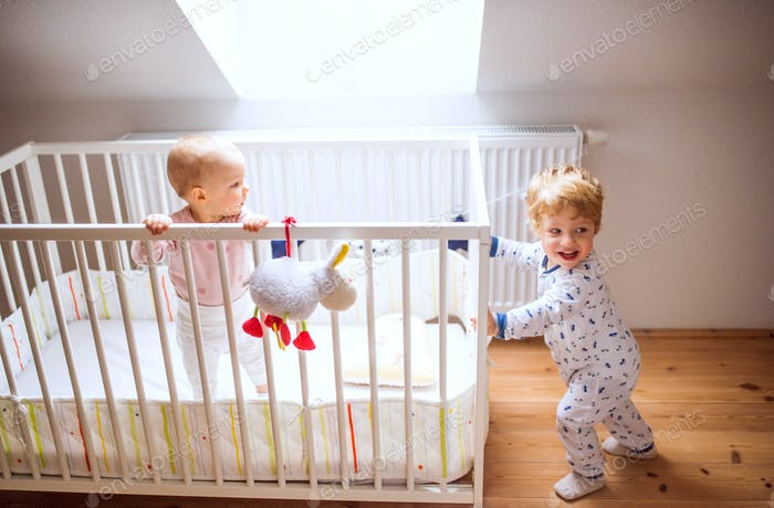Two toddler children in bedroom at home.