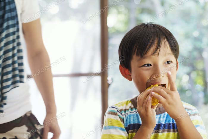 Close up of boy with black hair eating corn on the cob.
