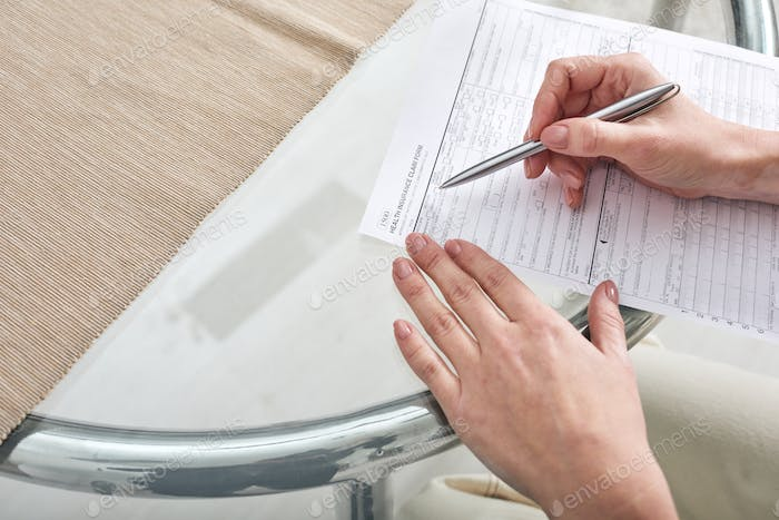 Hands of young female with pen over paper filling in health insurance claim form