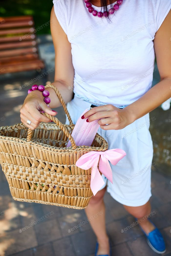 Hand of trendy woman in with straw bag with pink medical mask in handbag outdoors