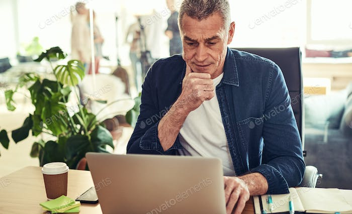 Mature businessman deep in thought at his office desk