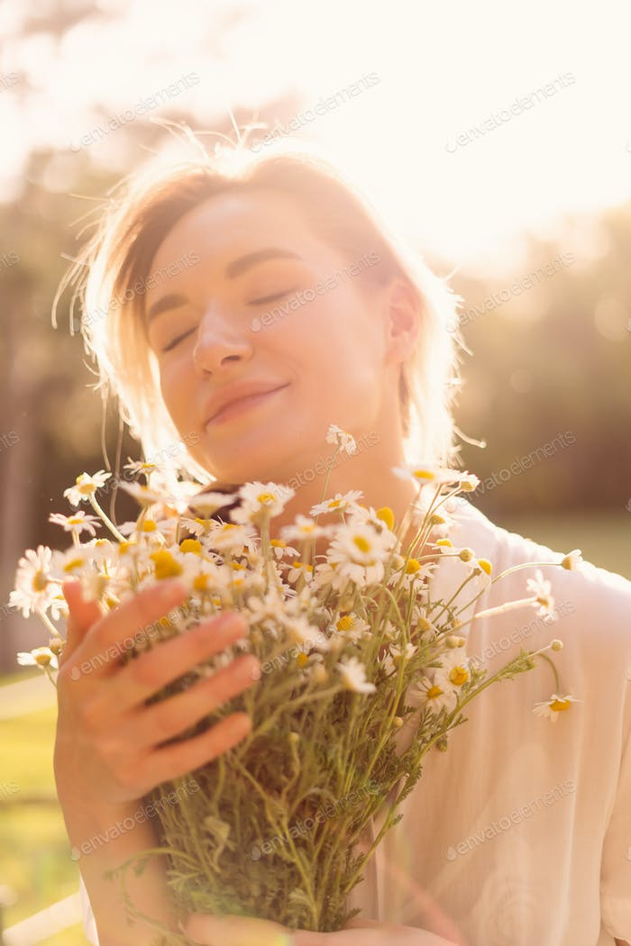 Beautiful woman with chamomile flowers