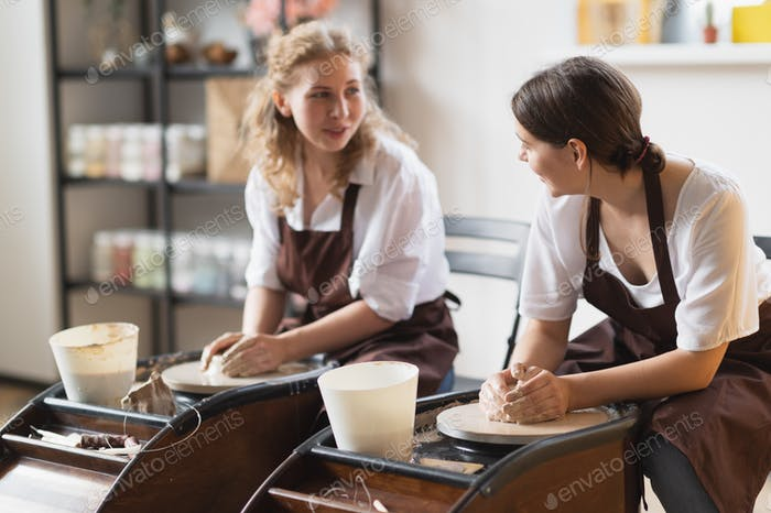 Two girls working on potters wheel making clay handmade craft in pottery workshop, friendship and