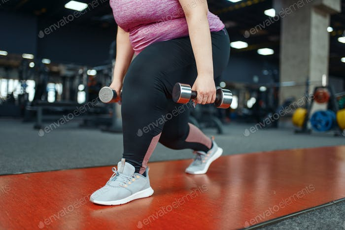 Overweight woman, exercise with dumbbells in gym