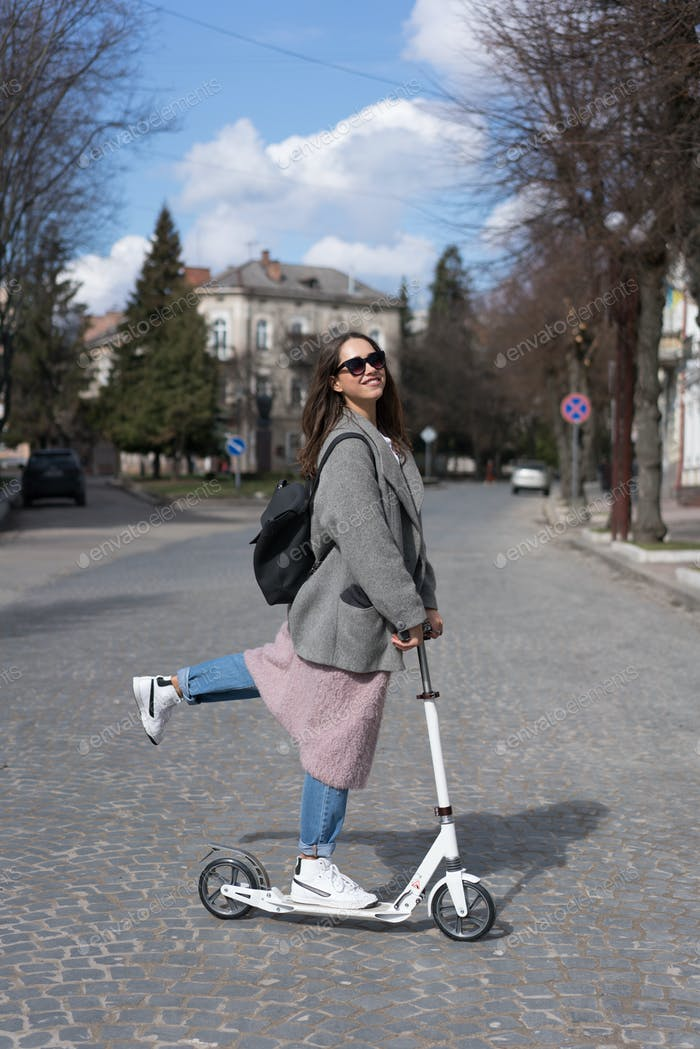 Young girl posing on a scooter
