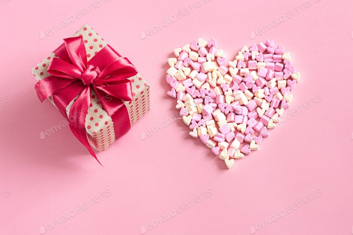 The concept of Valentine's day. Gift box with red bow on pink background.