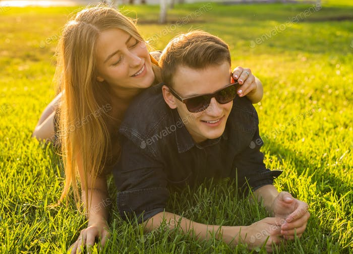 young couple having fun and playing in grass. woman lying over her lover, smiling