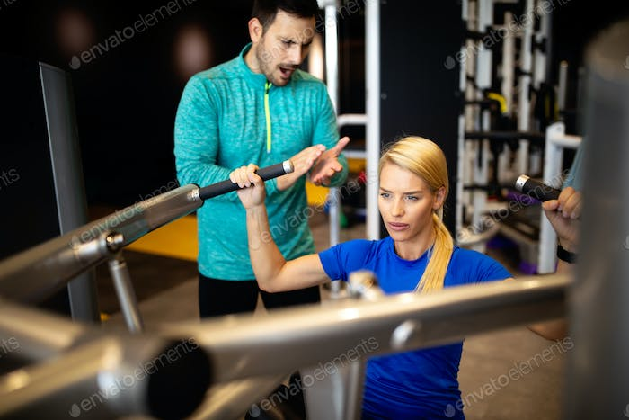 Woman with her personal fitness trainer in the gym exercising