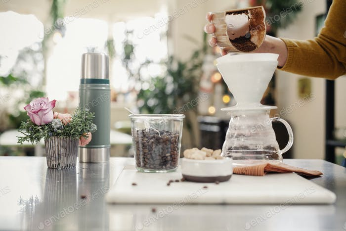 A person making filter coffee in a kitchen.