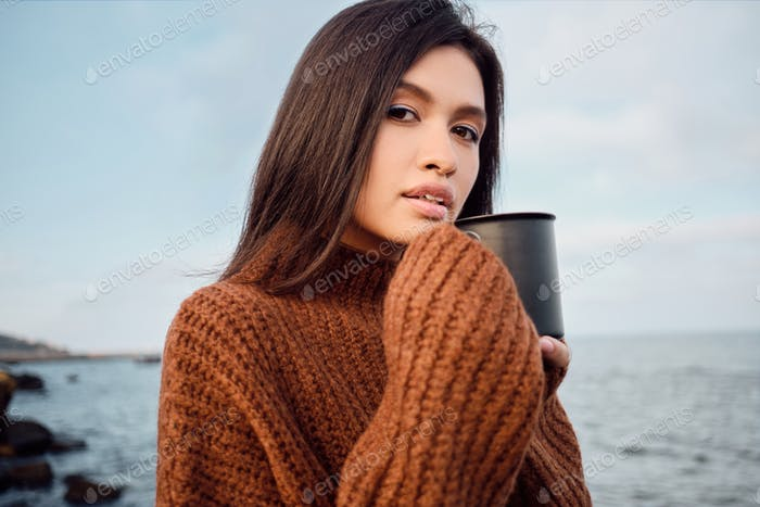 Beautiful Asian girl in knitted sweater with mug in hands intently looking in camera on seaside