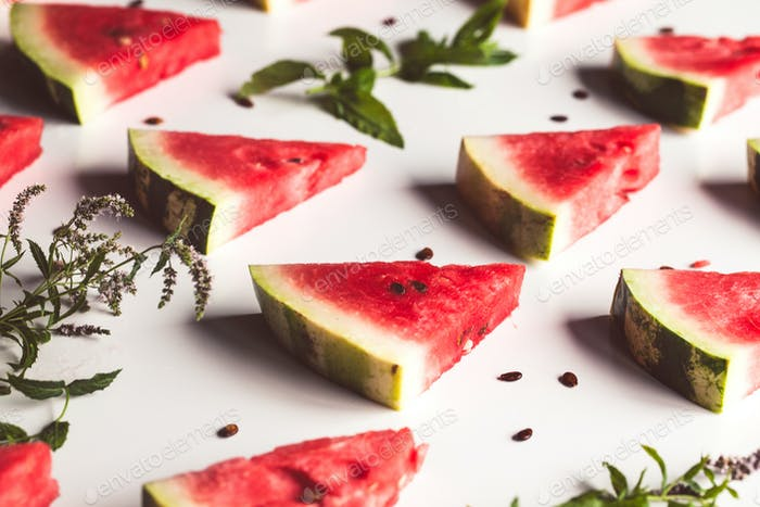 geschnittene dreieckige Scheiben von reifen roten Wassermelone mit Samen mit grünen Minzblättern, Limette