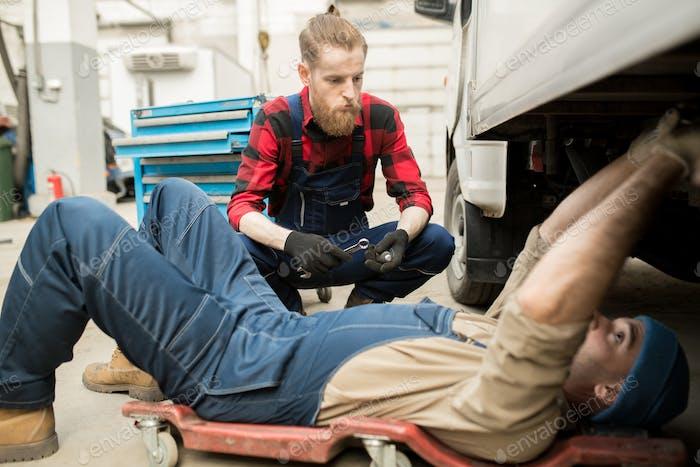 Mechanics Repairing Vehicle In Garage