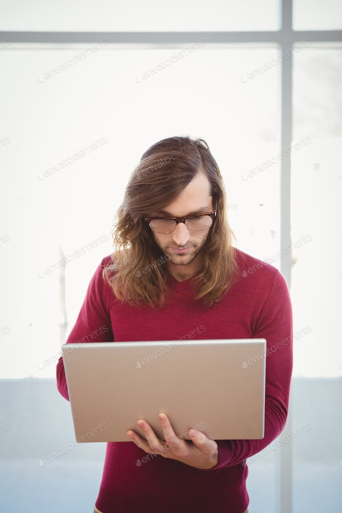 Man using laptop while standing against window in office