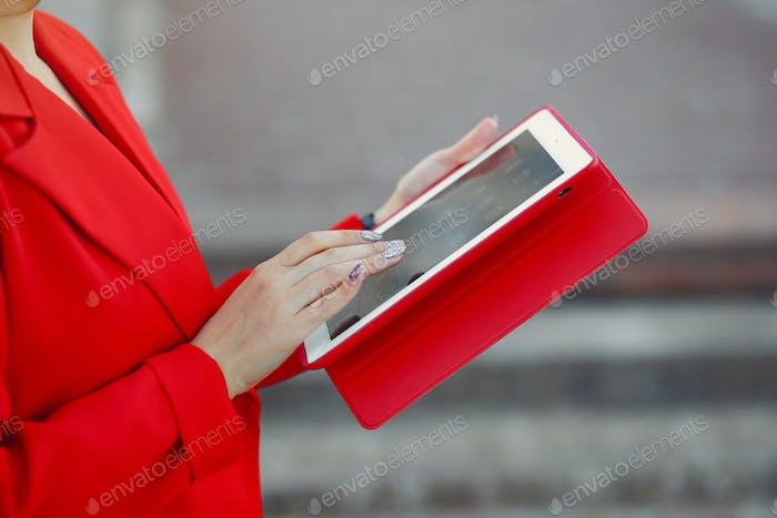 Frau in der roten Jacke verwenden Sie eine Tablette