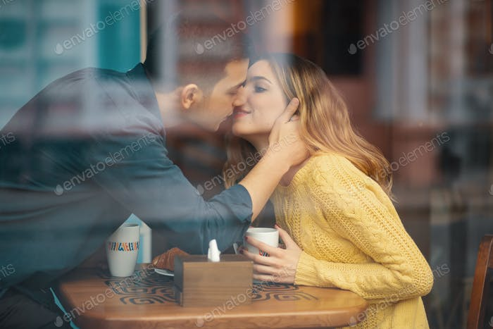 Young attractive couple on date in coffee shop kissing