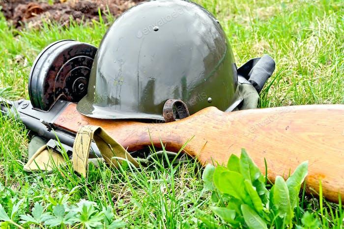 Helmet and submachine gun on grass