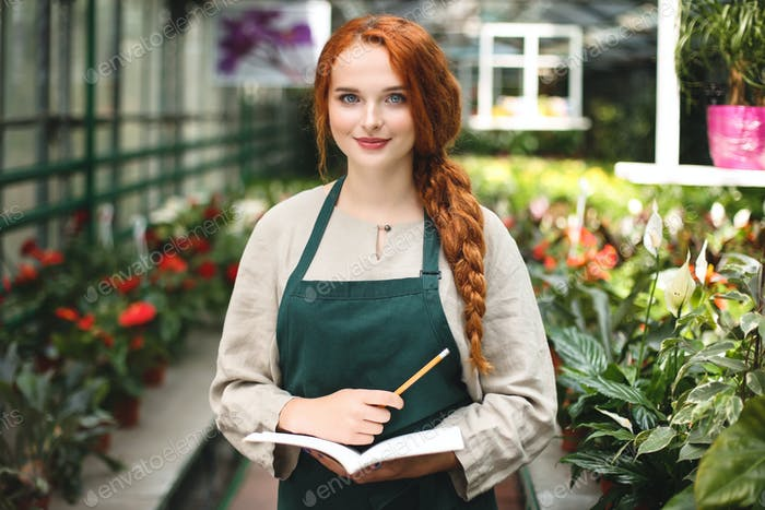 Young smiling florist in apron standing with notepad and pencil in hands