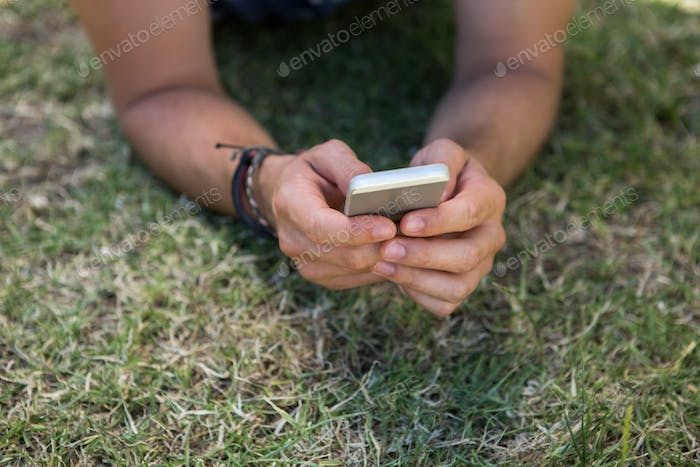 Man using phone in park on a summers day