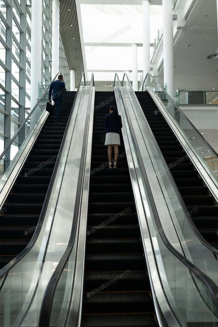 Rear view of businessman and businesswoman moving upwards on escalator in office lobby