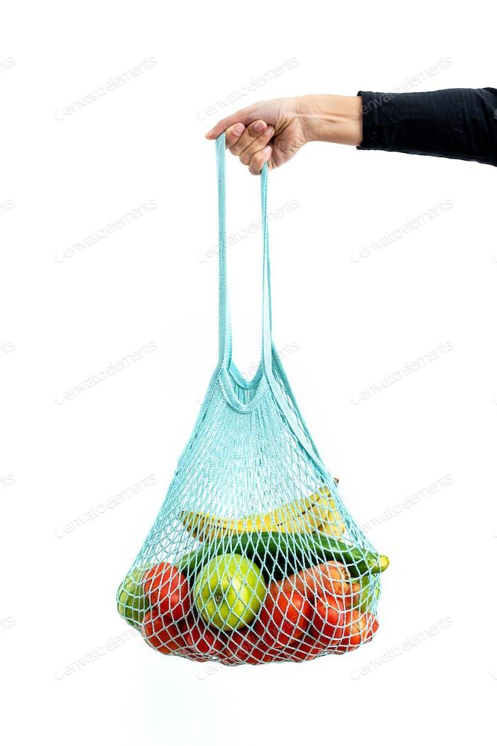 Mädchen hält wiederverwendbare Mesh-Tasche voller Bio-Gemüse