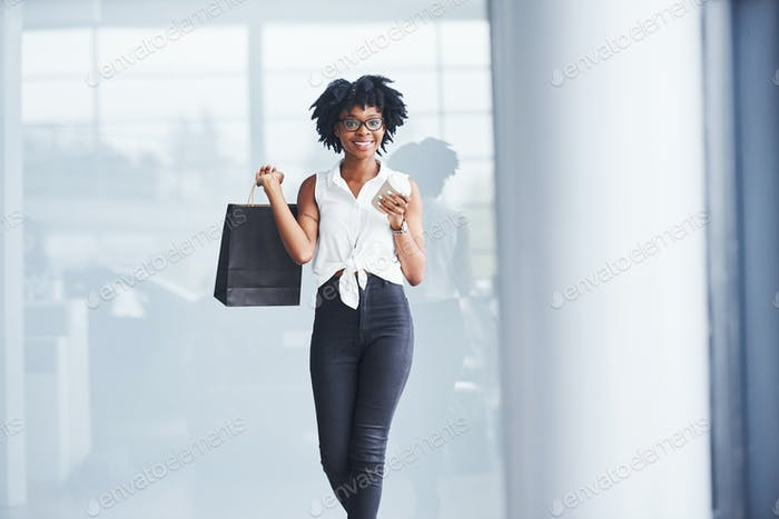 Young african american woman in glasses stands indoors with package in hands