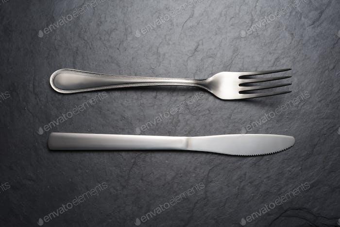 Fork and knife on black slate background