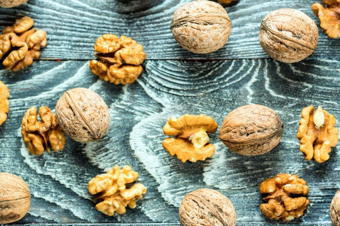 Walnuts and kernels on burlap on wooden backgound