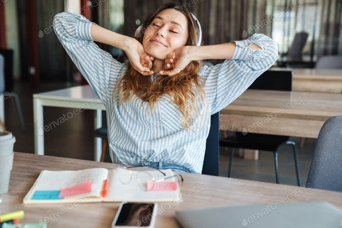 Image of relaxed young woman using headphones and stretching her body