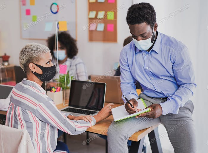 Young multiracial people wearing protective face mask at work in office - Prevention for coronavirus