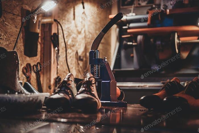 Elderly designer is working on pair of shoes