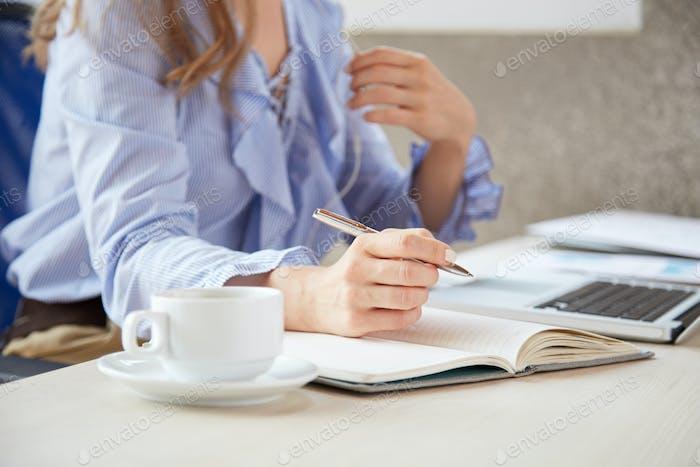 Geschäftsfrau im Planer schreiben