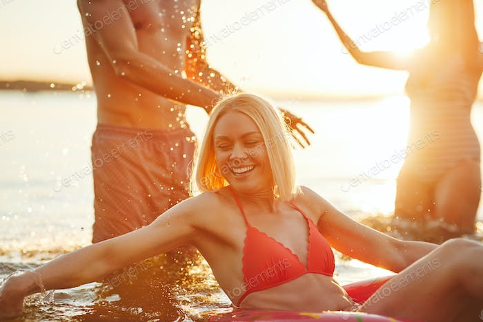 Smiling young woman and friends splashing water in a lake