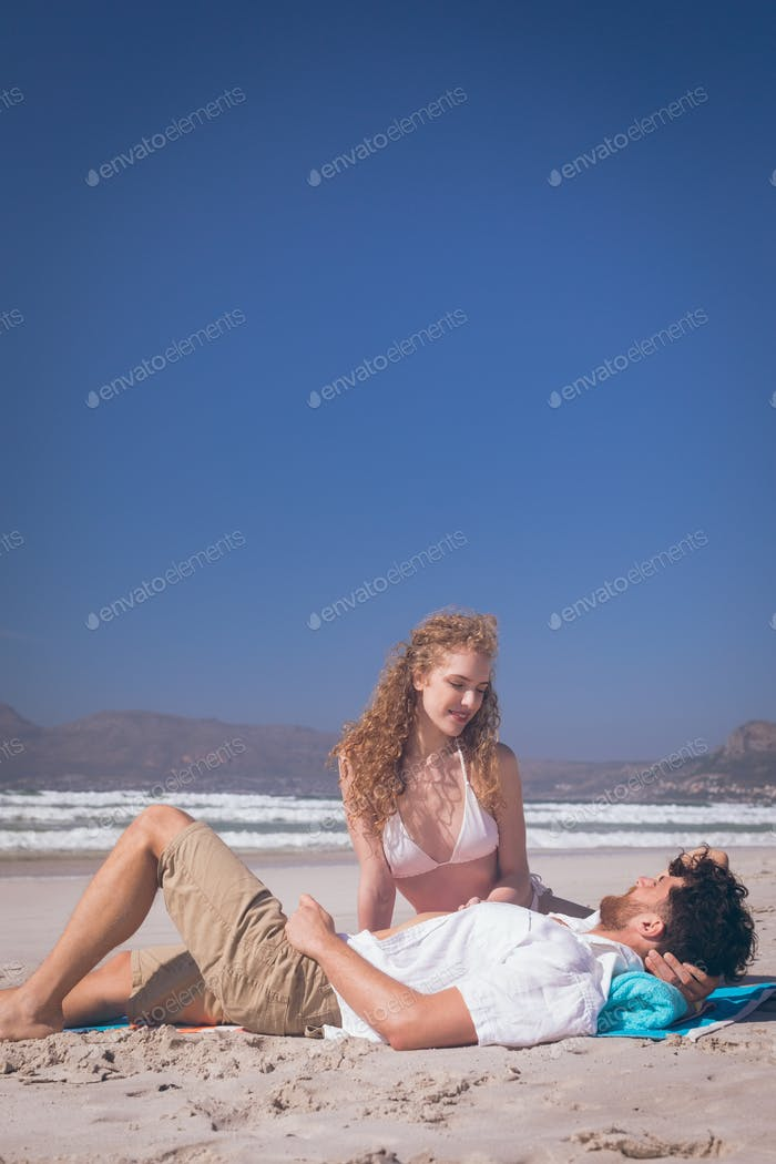 Romantic couple interacting with each other at beach on a sunny day. They are smiling