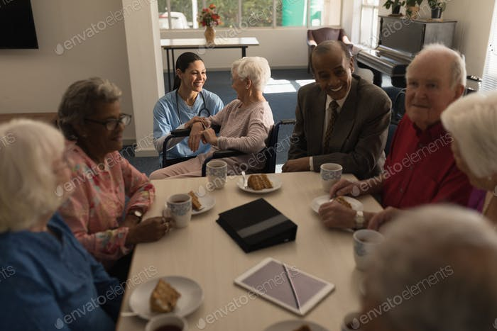 Front view of group of senior friends having breakfast on dining table at nursing home