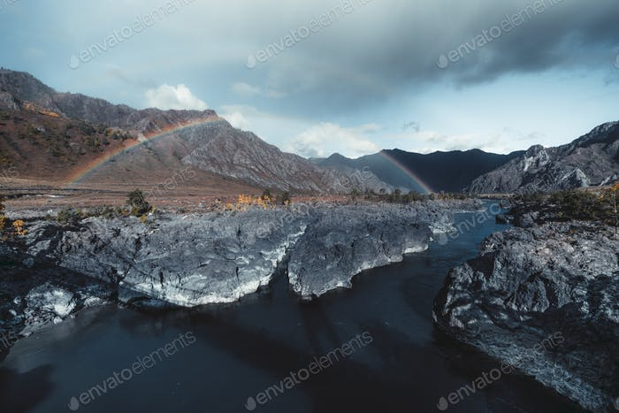 Double rainbow in mountains, river