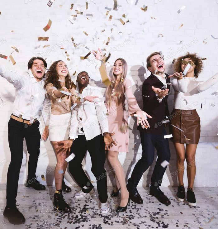 Young People Having Party With Falling Confetti Having Fun Indoors
