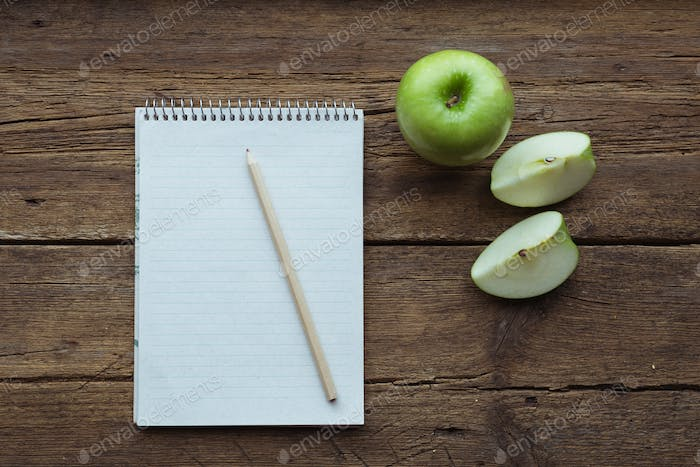 Top view of green apple, notepad and pencil on wooden background