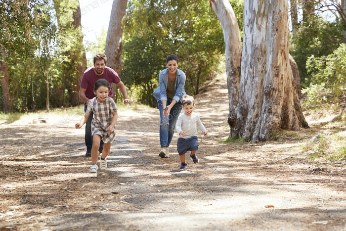 Family Running Along Path Through Forest Together