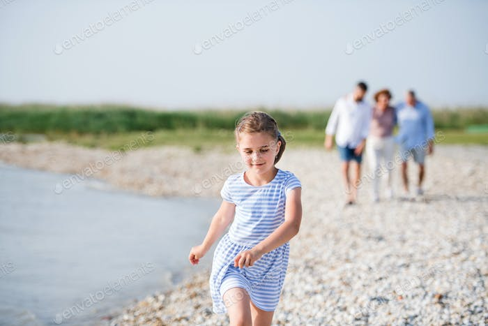 Small girl with family on a holiday walking by the lake, holding hands