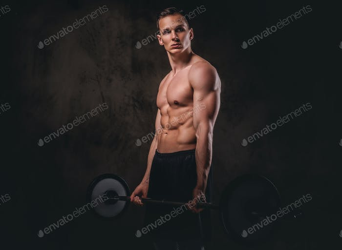 Portrait of a handsome young bodybuilder on dark background.