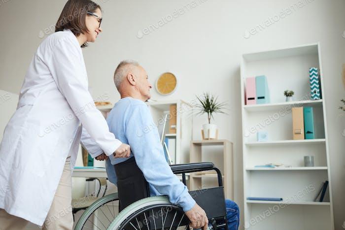 Nurse Helping Disabled Old Man