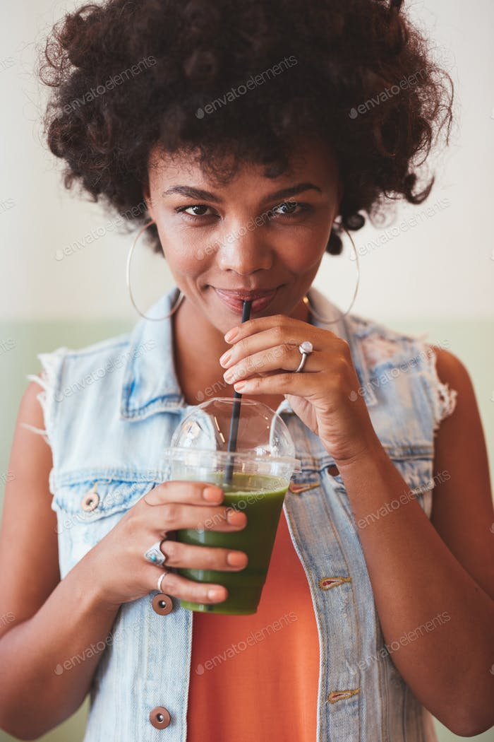 Attractive african woman drinking fresh fruit juice