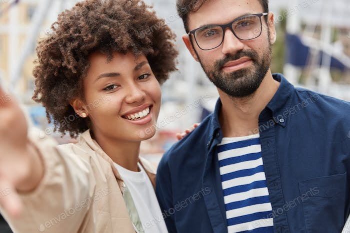 Outdoor shot of lovely mixed race couple have stroll together, stand next to each other, pose for ma
