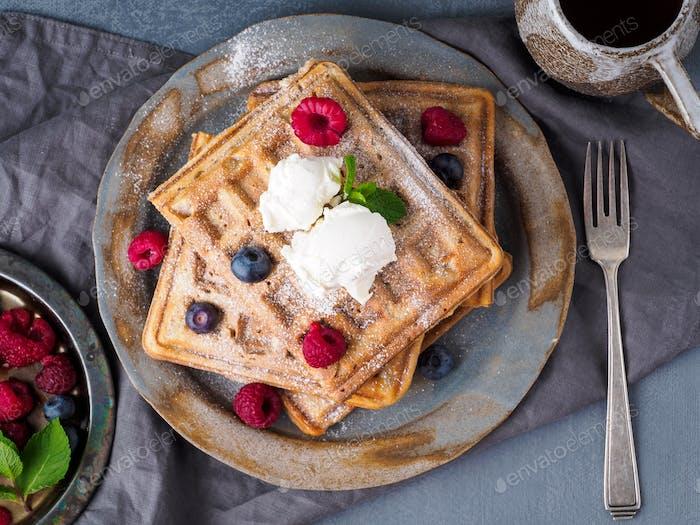 Belgian waffles with raspberries, chocolate syrup. Breakfast with tea