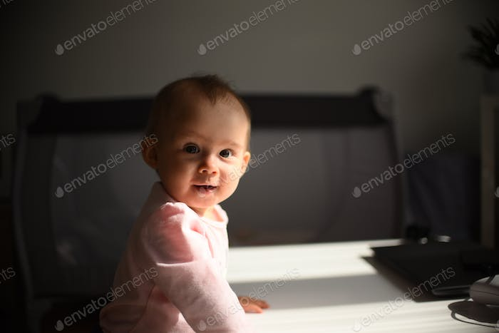 Baby girl stands next to cafe table in living room