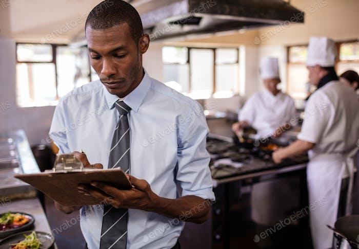 Gerente masculino escribiendo en un clipbaord en la Cocina en el hotel