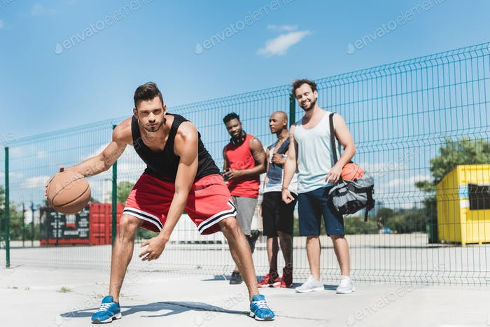 group of young multicultural men playing basketball on court